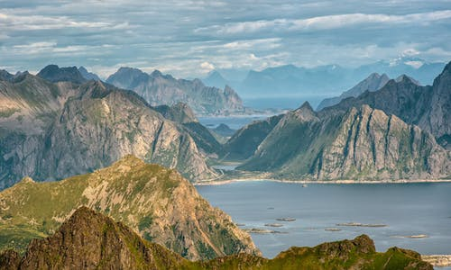 Magnificent landscape of rocky mountains in calm ocean against cloudy sky in Norway