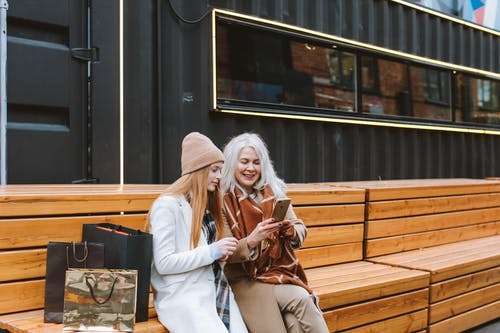 Woman in White Coat Sitting on Brown Wooden Bench