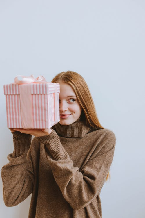 Woman in Brown Sweater Holding Pink and White Plastic Container