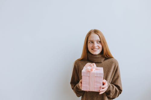 Smiling Woman carrying Pink Gift Box