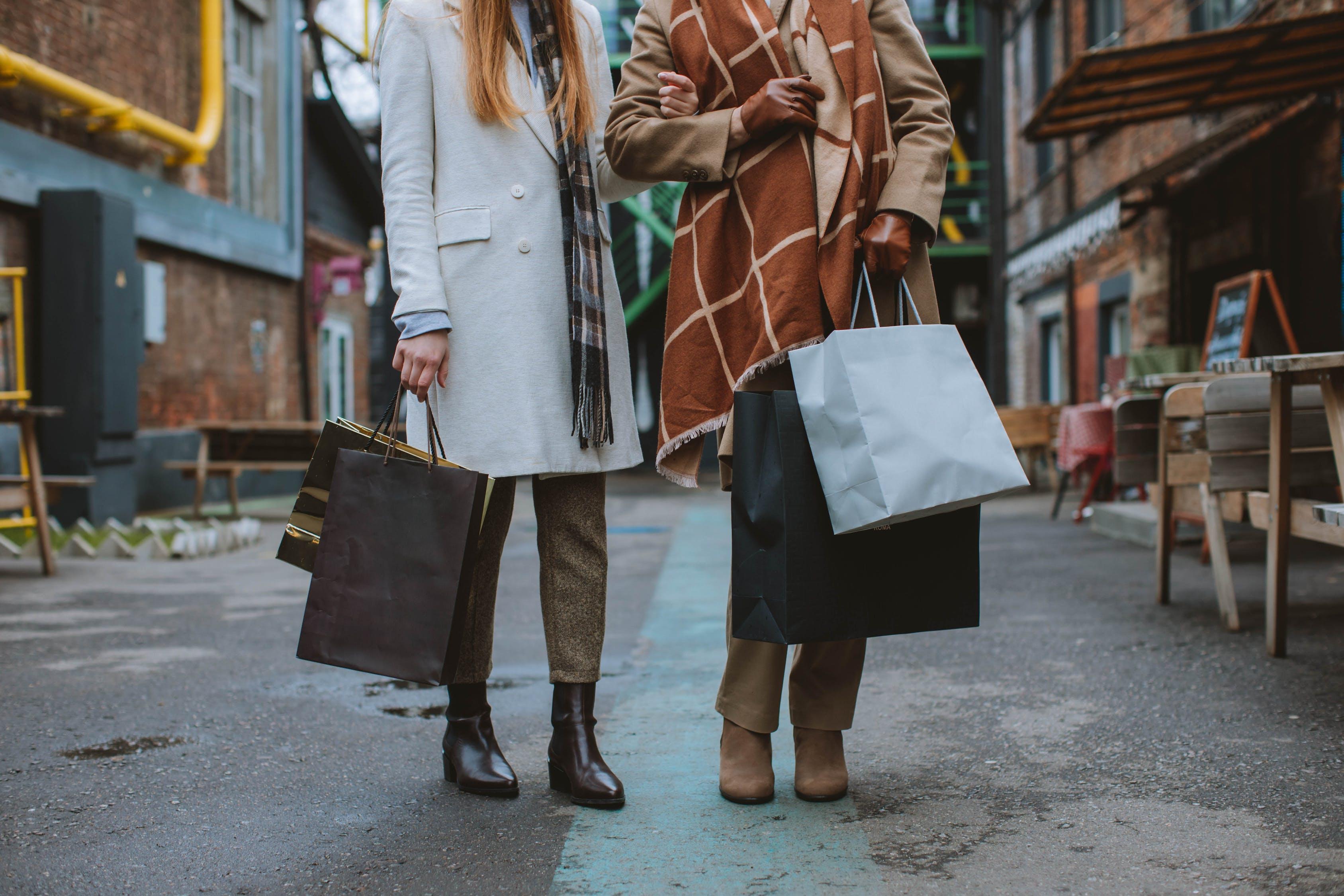 Woman in Brown Coat Holding Black Paper Bag