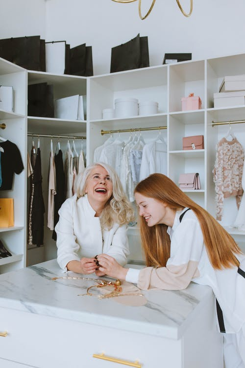 Woman in White Dress Shirt Sitting Beside Woman in White Dress Shirt