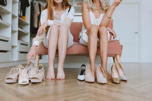 2 Women in White Dress Sitting on Brown Wooden Floor