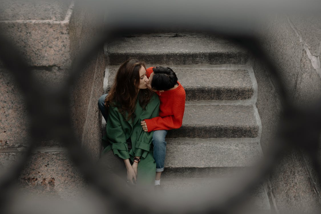 Woman in Red Jacket and Green Pants Sitting on Concrete Stairs
