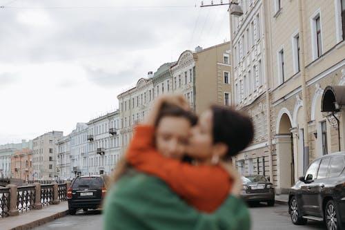 Woman in Green Jacket Carrying Baby in Orange Jacket