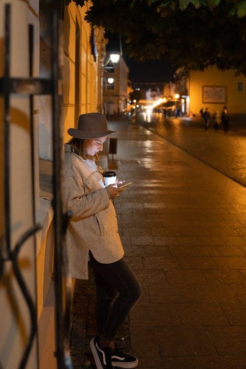 Man in Brown Coat and Black Pants Wearing Brown Hat Standing on Sidewalk during Night Time