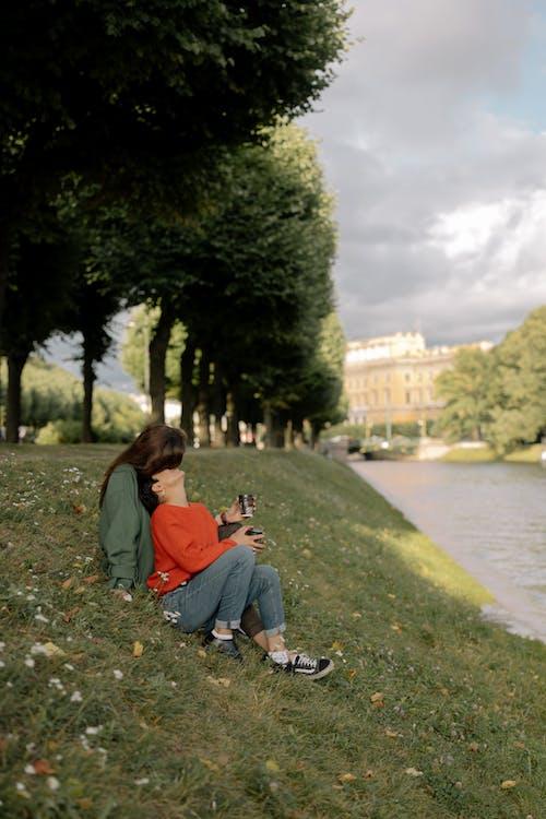 Woman in Orange Shirt Sitting on Green Grass Field Near River