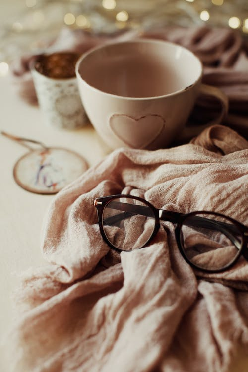 Cup and eyeglasses on pink scarf