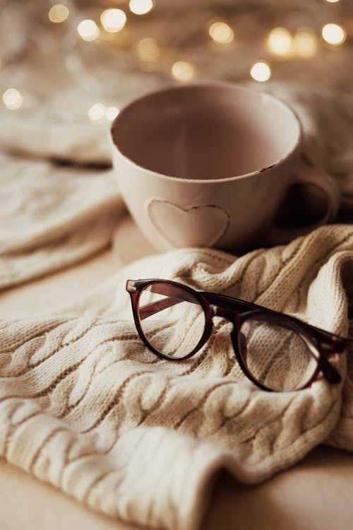Empty cup and eyeglasses on plaid