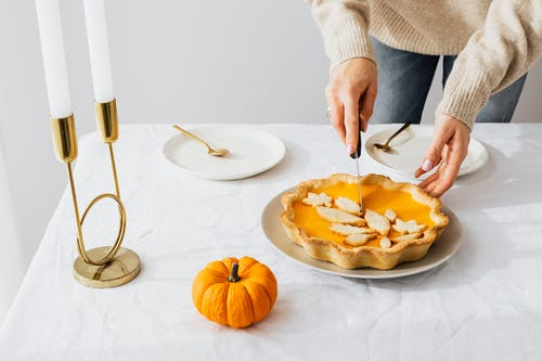 Person Slicing Orange Fruit on White Ceramic Plate