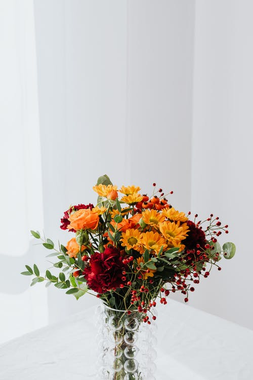 Red and Yellow Flowers on White Table
