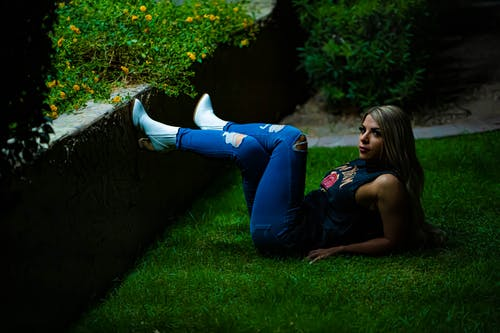 Woman in Blue Tank Top and Blue Denim Jeans Lying on Green Grass Field