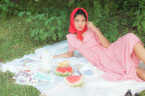 Girl in Red and White Polka Dot Dress Sitting on White Textile