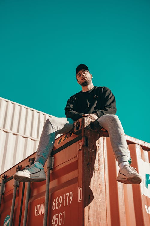 Bearded man sitting on orange cargo container on sunny day