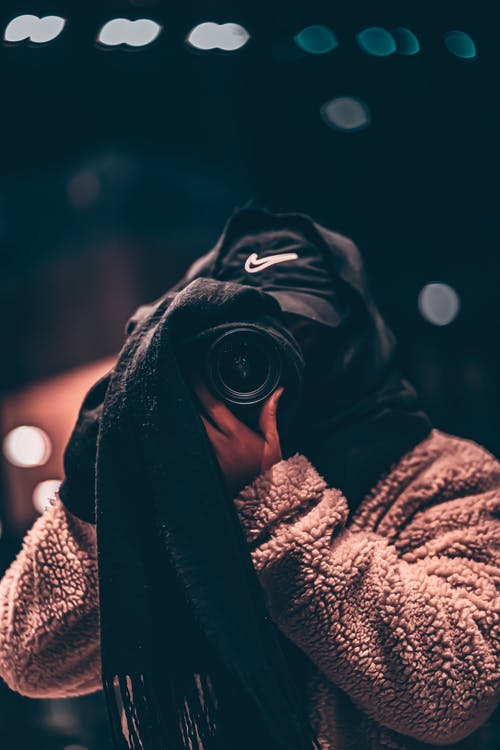 Faceless photographer in warm clothes taking photo