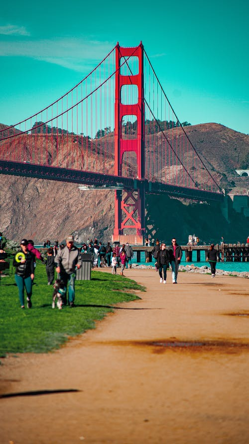 People walking under Golden Gate bridge in San Francisco