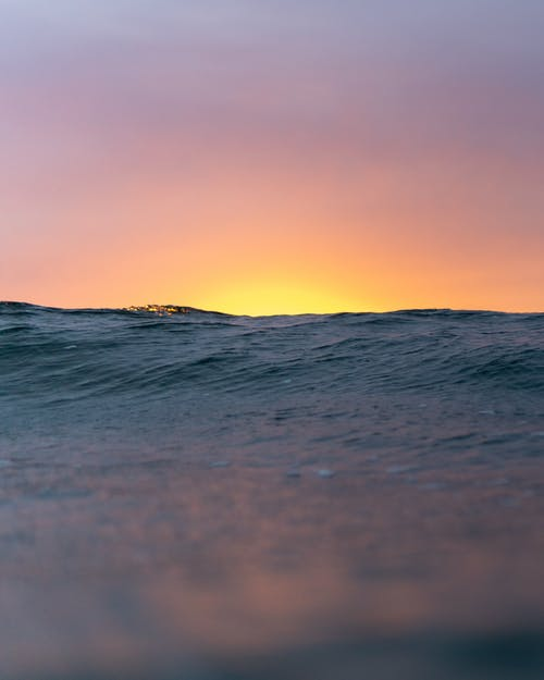 Wavy ocean with rippling surface against bright sunlight over horizon at sunset time