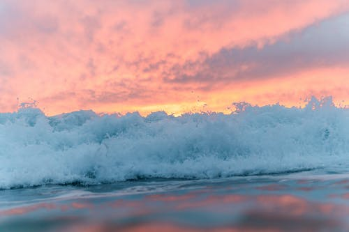Foamy sea under colorful sky at sunset