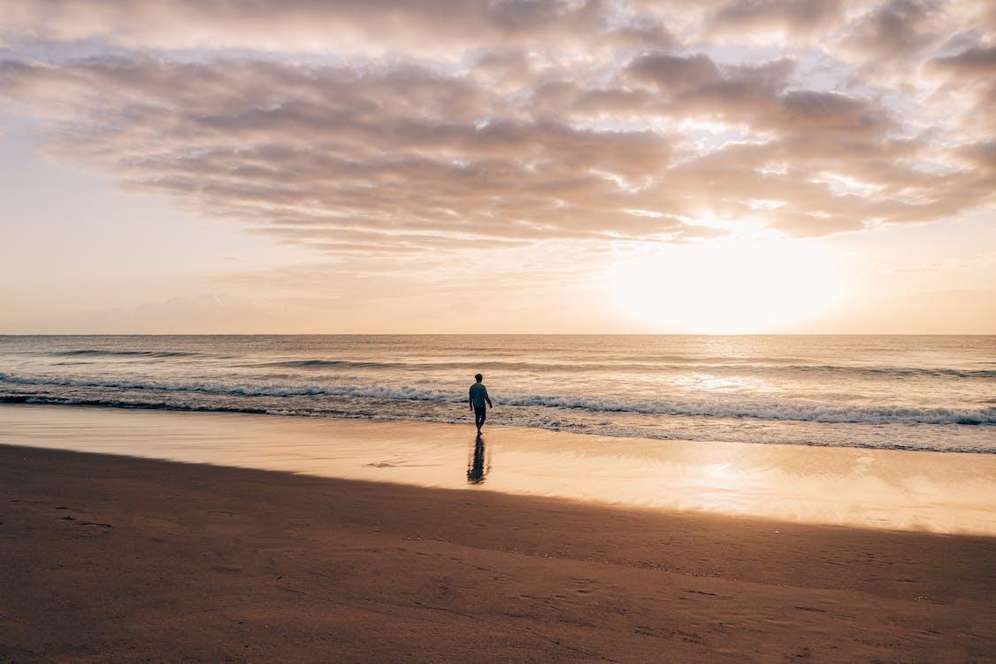 Lonely person walking on empty seashore