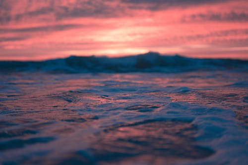 Bright sky with colorful clouds above wavy sea with foam at sunrise time