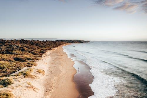 Rocky coast with sandy beach and wavy sea