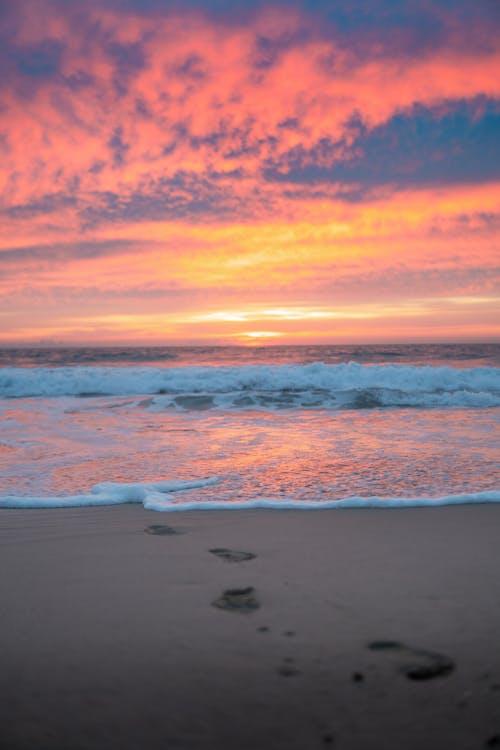 Footprints on sandy beach near sea at sunset
