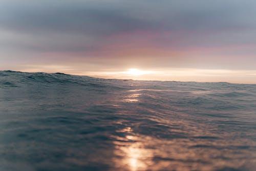 Cloudy sunset sky over wavy sea