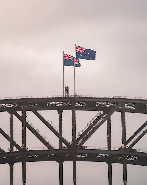 Scenery of national Australian flags waving on majestic Sydney Harbor Bridge arch trusses under gray sky at dusk