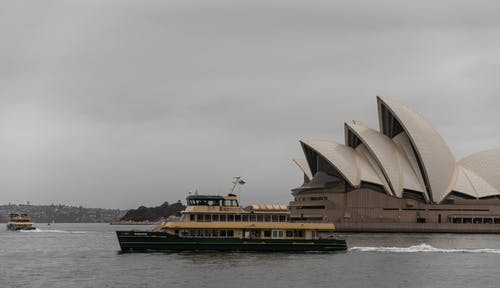 Cruise ship floating along majestic Sydney Opera House in twilight