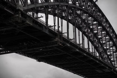 Black and white from below famous Sydney Harbor Bridge with arch trusses beneath gloomy sky