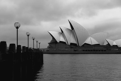 Black and white geometrical facade of modern Sydney Opera House in expressionism style located on embankment on cloudy day