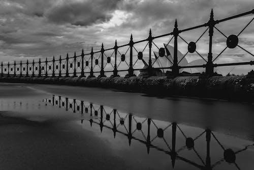 Black and white famous white Sydney Opera House behind embankment metal railing on overcast rainy day