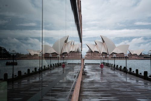 Glass building reflecting majestic Sydney Opera House facade with white unusual panels located on city harbor in daylight