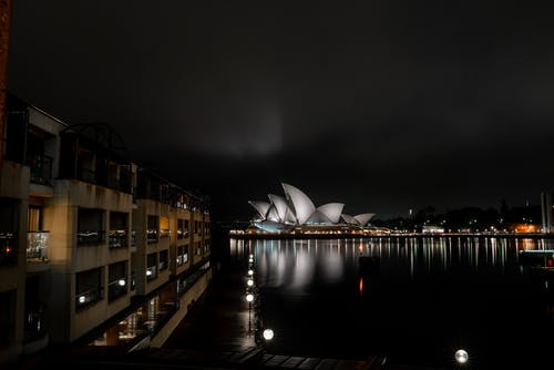 Exterior of glossy white futuristic Sydney Opera House illuminated by luminous lights and located on city embankment at night