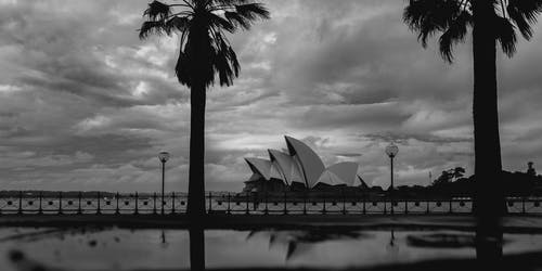 Black and white facade of white geometric Sydney Opera House located near city promenade on cloudy gloomy weather