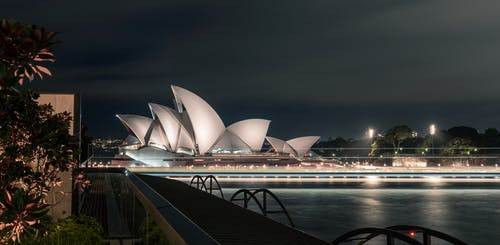 Unusual design of white Sydney Opera House with large concrete panels forming shells located on city harbor at night