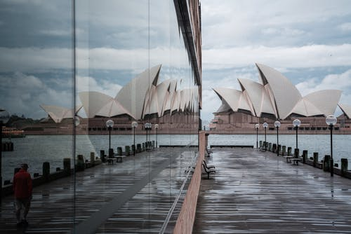 Exterior of modern white Sydney Opera House with unusual futuristic design located on city harbor and reflecting in neighbor building glass wall in daylight