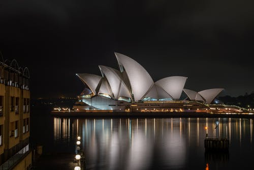 Glossy white facade of majestic Sydney Opera House in expressionism style reflecting in calm river water at dark night