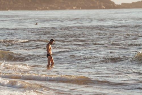 물결 치는 바닷물에 서있는 수영복에 남자