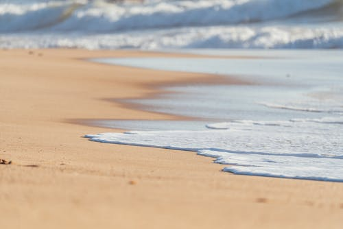 Sandy smooth coast washed by foamy peaceful waves of deep powerful ocean in sunlight