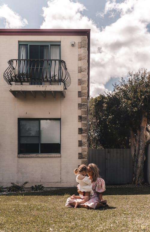 Madre E Hija Sentadas En El Césped