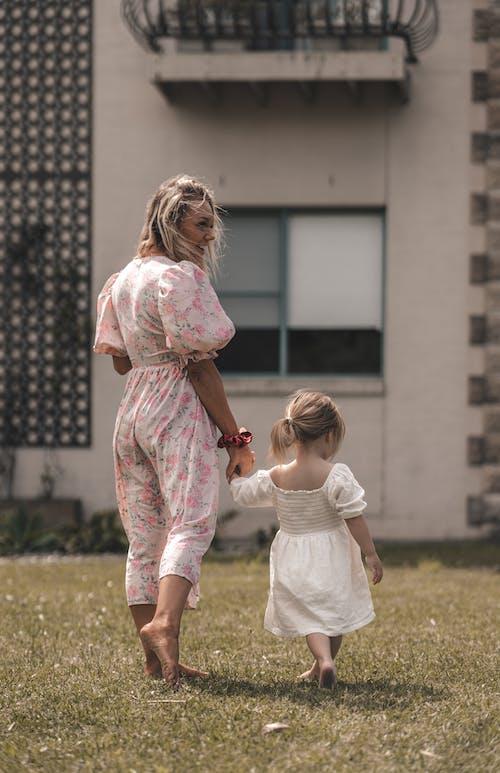 Madre Con Hija Caminando Sobre La Hierba Cerca Del Edificio