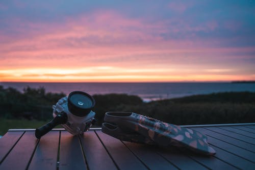 Action camera placed near flippers on wooden table in nature on seaside against grassy lawn and sunset sky over sea with blurred background