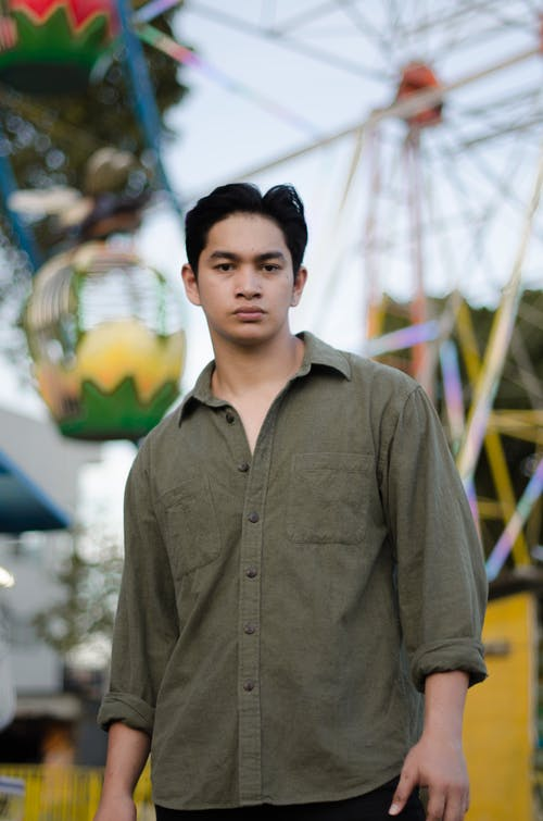 Emotionless Asian male in brown shirt standing against Ferris wheel in entertainment park and looking at camera