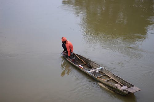Man in Red Shirt and Black Pants on Brown Wooden Boat on Body of Water during