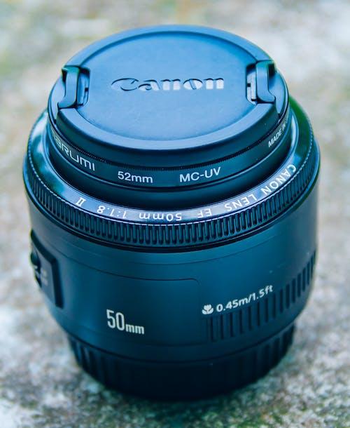 Black Nikon Camera Lens on White Textile