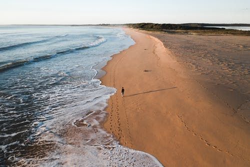 From above of distant traveler walking along sandy coastline near foamy sea on summer day in tropical country in nature