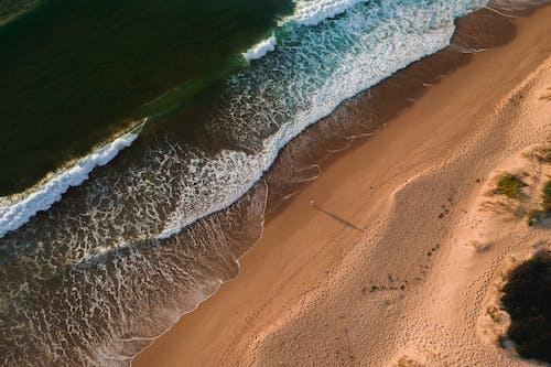 Sandy beach with waving sea
