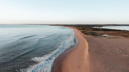 Sandy coast against cloudless sky