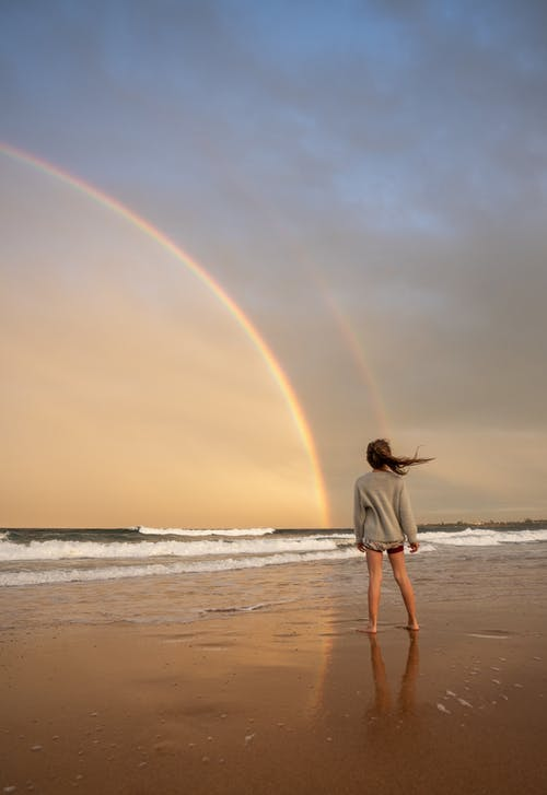Full body of anonymous barefoot female with flying hair standing on sandy coast near waving sea against colorful rainbow in nature